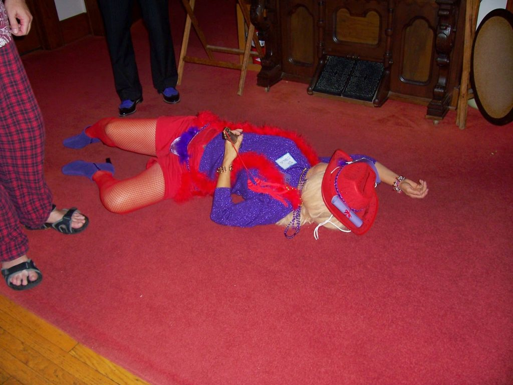 woman in costume lying on floor with knife