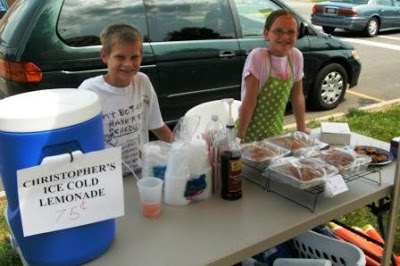 two kids selling lemonade and baked goods