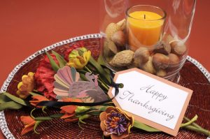"""Festive fall centerpiece with a card that says, """"Happy Thanksgiving."""""""