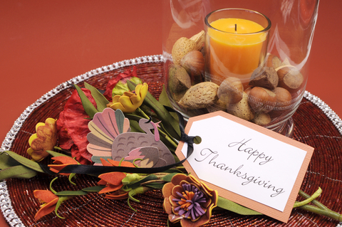 "Festive fall centerpiece with a card that says, ""Happy Thanksgiving."""