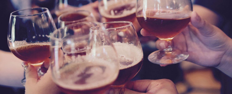 several hands toasting beer glasses