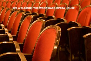 """See a Classic: Woodward Opera House"" text overlay on red theater chairs"