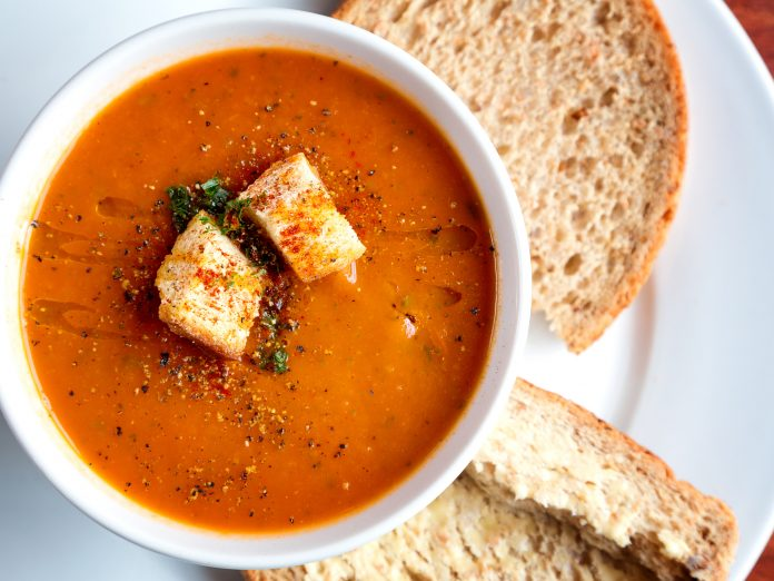 A bowl of fresh tomato soup in white ceramic bowl, garnished with herbs, croutons, seasoning and a drizzle of olive oil, and served with crusty wholemeal bread at Rebecca's Bistro.
