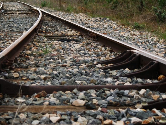 railroad tracks with rocks and vegetation in the background. ohio's rails-to-trails turns old rails into new trails.