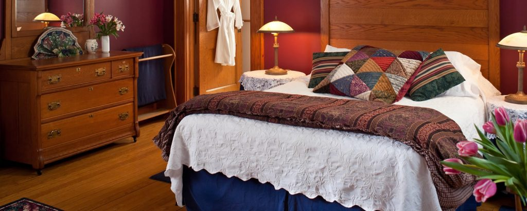 A king size bed with classic furniture in the White Oak Room at the White Oak Inn.