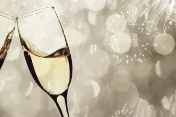 A champagne toast against sparkles