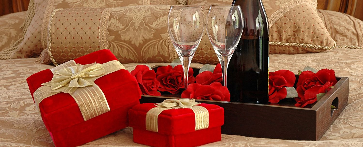 Romantic flowers and wine on a bed