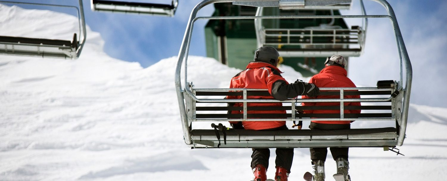 A couple riding a ski lift at the Snow Trails Ski Resort.