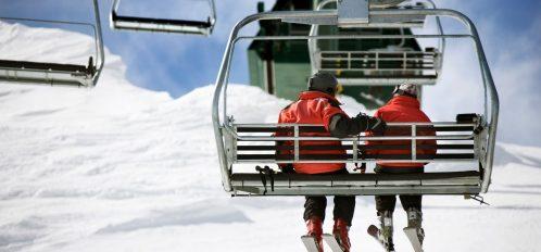 A couple riding a ski lift at the Snow Trails Ski Resort.