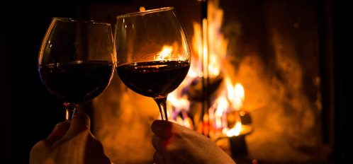 Couple holding pair of glasses with wine at fire pit on a romantic getaway in Ohio.