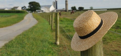 closeup of Amish straw hat laying over farm fence post