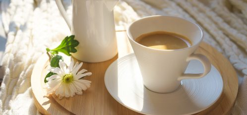 white cup of coffee with cozy knitted plaid on a round wooden desk and with white flower