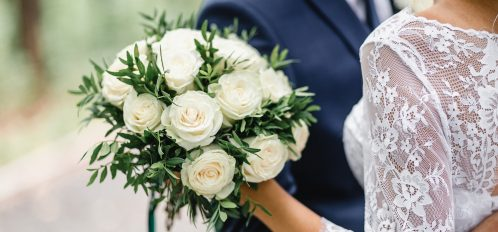 Bride and groom holding flowers.