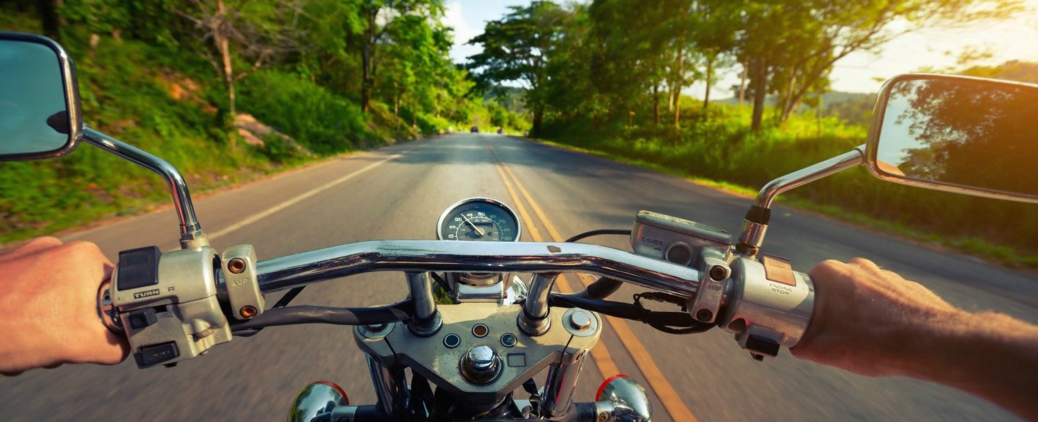 Driver riding motorcycle on an asphalt road through forest